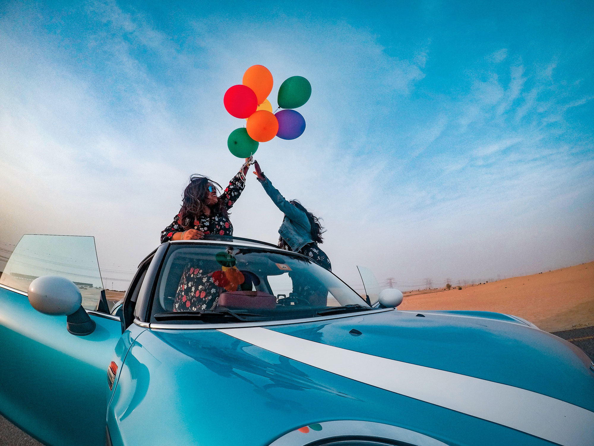 two women with balloons in a sports car